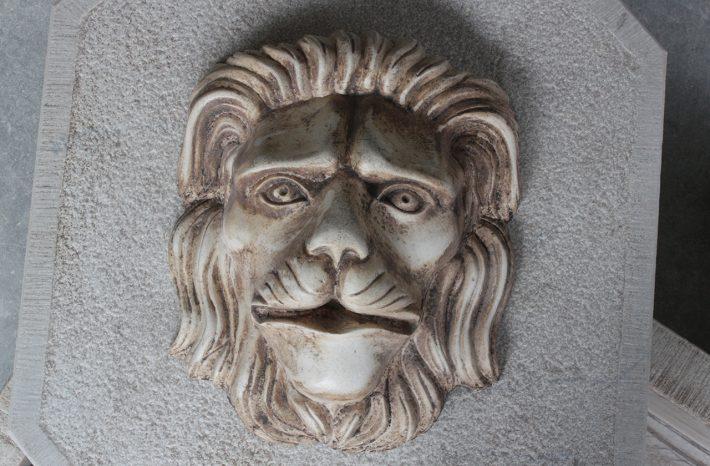 Testa di leone a basso rilievo in pietra bianca levigata e anticata.