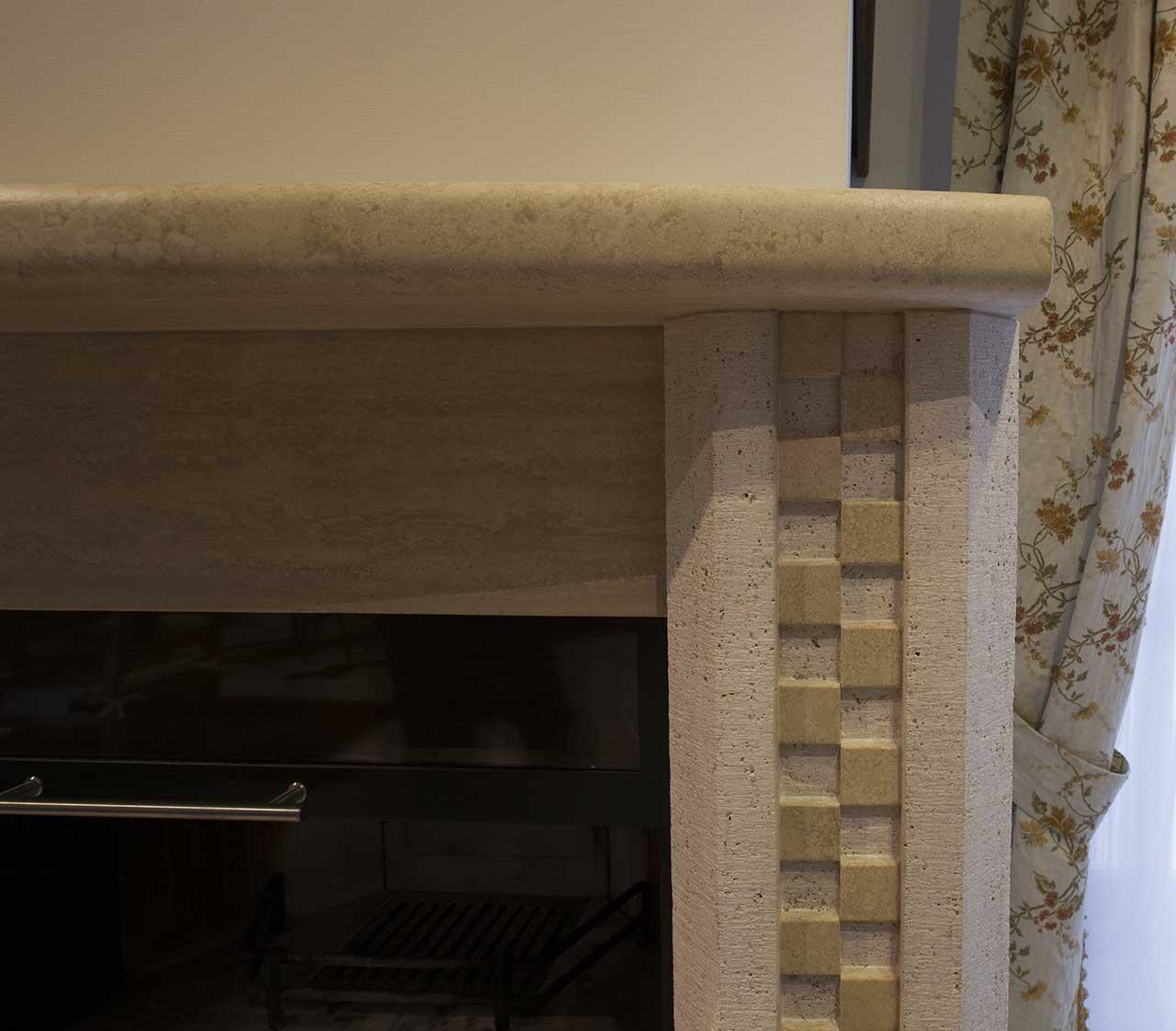Particolare camino a parete in pietra travertino Oniciato levigata e scalpellata.