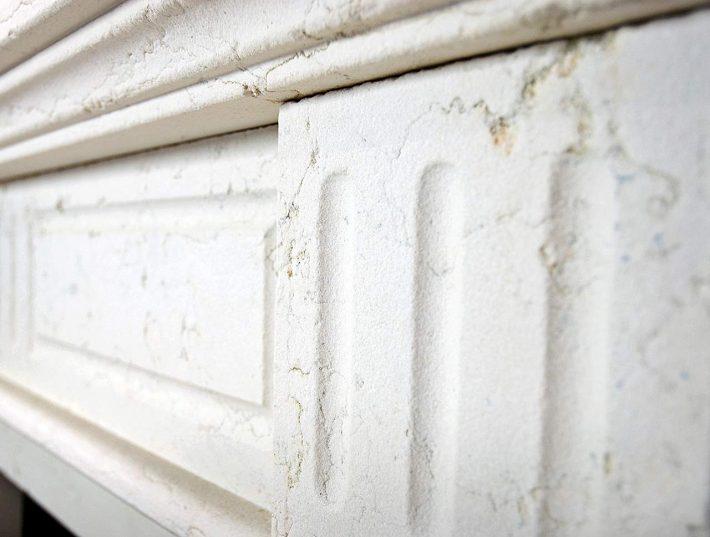 Particolare camino a parete in pietra bianco perlino sabbiata.